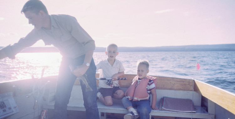 A dad in a fishing boat with two little boys